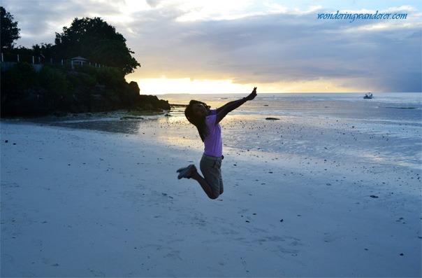 Woman jumping in Alona Beach Bohol